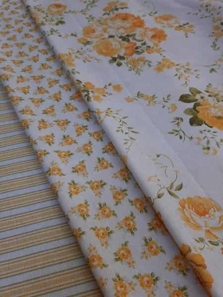 υφάσματα με λουλούδια πορτοκαλί κίτρινα συνδυασμένα μεγάλα μπουκέτα και μικρά λουλουδάκια τύπου Λώρα Άσλευ και ρίγα όλα σε άσπροφόντο.