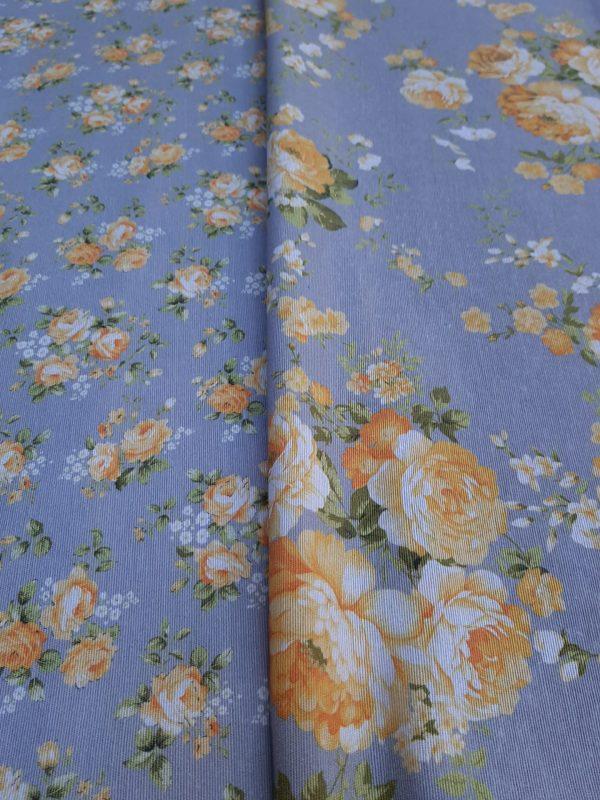 υφάσματα με λουλούδια πορτοκαλί κίτρινα συνδυασμένα μεγάλα μπουκέτα και μικρά λουλουδάκια τύπου Λώρα Άσλευ σε μπλέ φόντο.