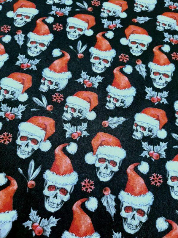 Ύφασμα βαμβακερό κρανία με κόκκινους σκούφους χριστουγεννιάτικους σε μαύρο φόντο